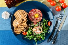Dish with beef tartare, tomatoes and leaves on the table with kn Stock Photos