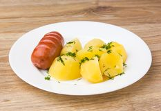 Fried sausage with boiled potatoes. A dish of boiled potatoes and fried sausages on a white plate Stock Photography