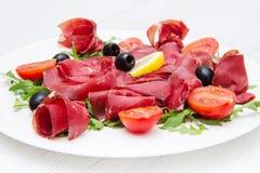 Dish of bresaola and aragula Stock Photos