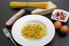 Dish with carbonara's spaghetti and ingredients Royalty Free Stock Images