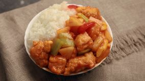 A dish of chicken with pineapple and rice. Sweet and Sour Chicken with pineapple and red bell peppers served with steamed rice. The dish rotates on the table stock video footage