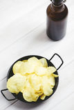 Dish with chips, beer bottle  on pale gray table. Vertical studio shot. Royalty Free Stock Photography