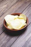 A dish with chips standing on dark gray colored wooden table. Stock Image