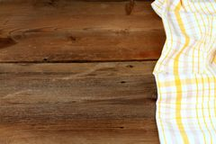 Dish cloth in yellow and white on brown wooden table Stock Image