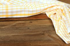 Dish cloth in yellow and white on brown wooden table Royalty Free Stock Photography