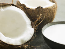 Dish of Coconut Milk with a Split Fresh Coconut Stock Image