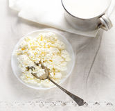 Dish of cottage cheese, a metal spoon and a mug of milk on a white background Royalty Free Stock Photo