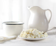 Dish of cottage cheese, a mug and a milk jug on a white background Royalty Free Stock Images