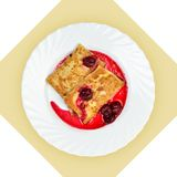 Dish of crepes with cherry sause on white plate. Stock Image