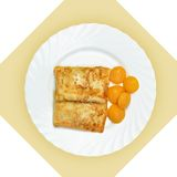 Dish of crepes with dried apricots on white plate. Stock Photography