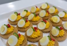 Dish with delicious appetizers with carrots cream, eggs and red caviar Stock Photography