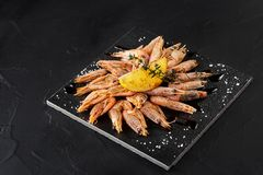 Dish with delicious grilled shrimps on table. Dish with delicious grilled shrimps with lemon on table. Copy space. Still life Stock Photography