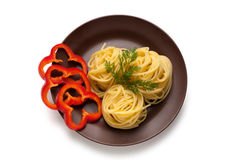 Dish with a delicious spaghetti and pepper. Cooked spaghetti with red peppers on a clay plate Royalty Free Stock Photos