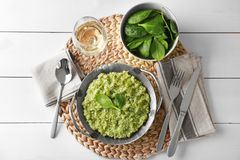Dish with delicious spinach risotto. On wooden table Stock Photo