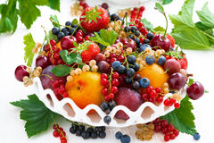 Dish with different fresh seasonal fruits and berries on white Stock Photo