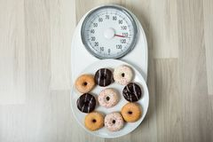 Dish Of Donuts On Weighing Scale. Elevated View Of Different Flavor Donuts On Plate Placed On Scale stock photography