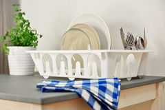 Dish drainer with plates and silverware. On a table. Focus on the dish drainer Royalty Free Stock Photo