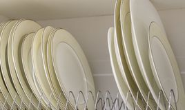 Dish drying metal rack with big nice white and light yellow clean plates on blurred background. Traditional comfortable kitchen.  stock photo