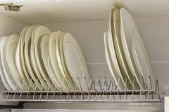 Dish drying metal rack with big nice white and light yellow clean plates on blurred background. Traditional comfortable kitchen.  royalty free stock photo