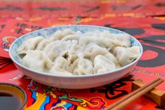 A dish of dumplings under the background of red couplets during the Spring Festival royalty free stock photo