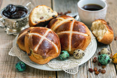 Dish with English Easter buns close up. Fresh Easter buns with raisins, colorful eggs and coffee Stock Images