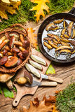 Dish with forest mushrooms and onions. On old wooden table Stock Photo