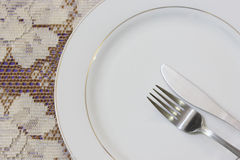 Dish with fork and knife with lacy tablecloth background Royalty Free Stock Photos