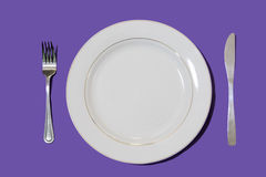Dish with fork and knife with purple background Stock Photo