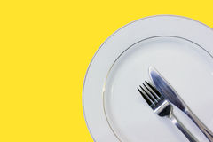 Dish with fork and knife with Yellow background Royalty Free Stock Photography