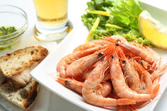 Dish of fresh boiled prawns. With lettuce, some bread and beer stock photo