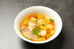 Dish with fresh homemade chicken soup on grey. Background royalty free stock photography