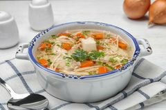 Dish with fresh homemade chicken soup served. On table stock image