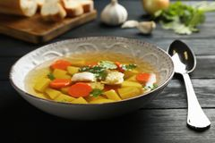 Dish with fresh homemade chicken soup. On wooden table royalty free stock image