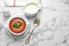 Dish with fresh homemade tomato soup on marble table, top view. Dish with fresh homemade tomato soup and space for text on marble table, top view stock images