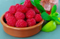 A dish of fresh ripe juicy raspberries, with mint and lime royalty free stock image