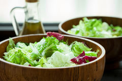 A dish of fresh salad frisse, Romano and radiccio with olive oil, salt and freshly ground percec in a wooden bowl Royalty Free Stock Images