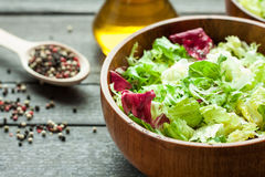 A dish of fresh salad frisse, Romano and radiccio with olive oil, salt and freshly ground percec in a wooden bowl Royalty Free Stock Photography