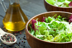 A dish of fresh salad frisse, Romano and radiccio with olive oil, salt and freshly ground percec in a wooden bowl Royalty Free Stock Photo