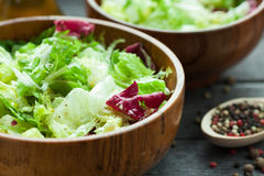 A dish of fresh salad frisse, Romano and radiccio with olive oil, salt and freshly ground percec in a wooden bowl Stock Image