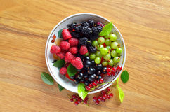 Dish of fresh seasonal berries. On wooden table,  top view Royalty Free Stock Photography