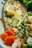 Fried fish with lemon and vegetables Stock Photography