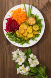 Dish with fried potatoes, beets, carrots and lettuce on a background of flowers. Wooden table. Close-up stock images