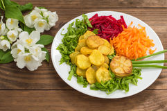 Dish with fried potatoes, beets, carrots and lettuce on a background of flowers. Wooden table. Close-up royalty free stock photo