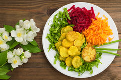 Dish with fried potatoes, beets, carrots and lettuce on a background of flowers. Wooden table. Close-up royalty free stock image