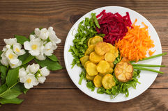 Dish with fried potatoes, beets, carrots and lettuce on a background of flowers. Wooden table. Close-up stock photos