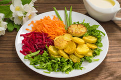 Dish with fried potatoes, beets, carrots and lettuce on a background of flowers. Wooden table. Close-up royalty free stock images