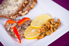Dish with fried prawns, bread and lemon. Starter with fried prawns with lemon, mashrooms and brown bread Stock Photo