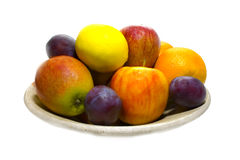 A dish of fruits. Some fruits like orange, apple , plum and lemon over white background Royalty Free Stock Photos