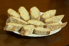 Dish full of bread slices. Over a wooden background Stock Image