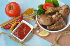 Dish full of fried chicken near tomato sauce, spices, seasoning. On blue background Stock Image
